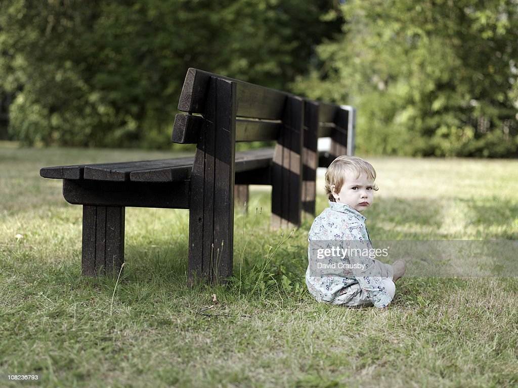 A bench andone year old boy : Stock Photo