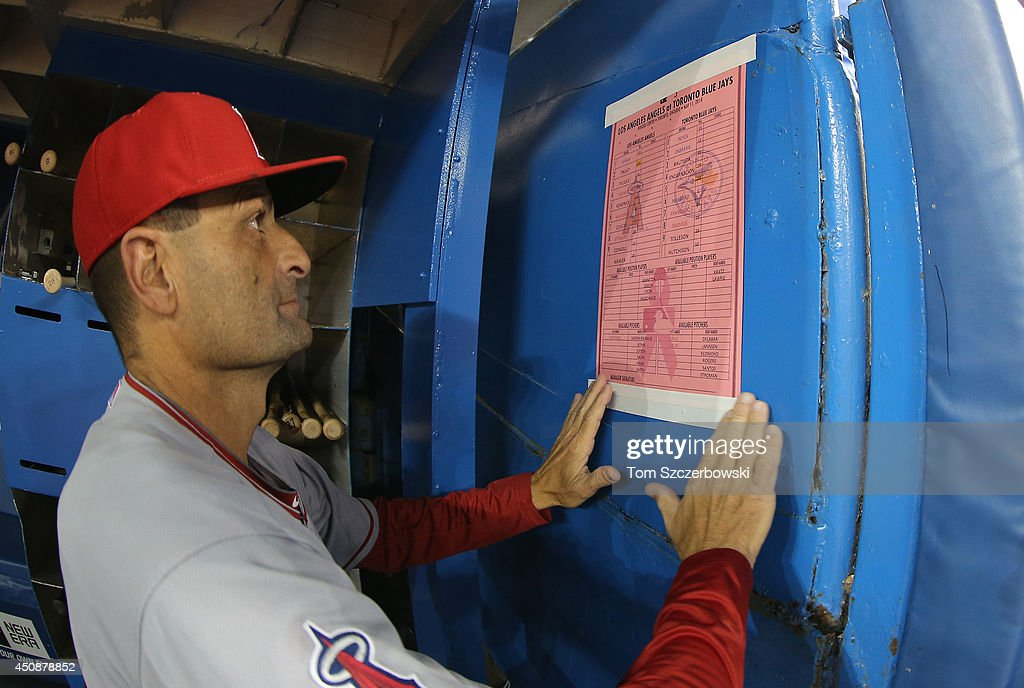 Bench coach Dino Ebel #21 of the Los Angeles Angels of Anaheim puts up a pink lineup on the dugout wall on Mother's Day before the start of an MLB game against the Toronto Blue Jays on May 11, 2014 at Rogers Centre in Toronto, Ontario, Canada.