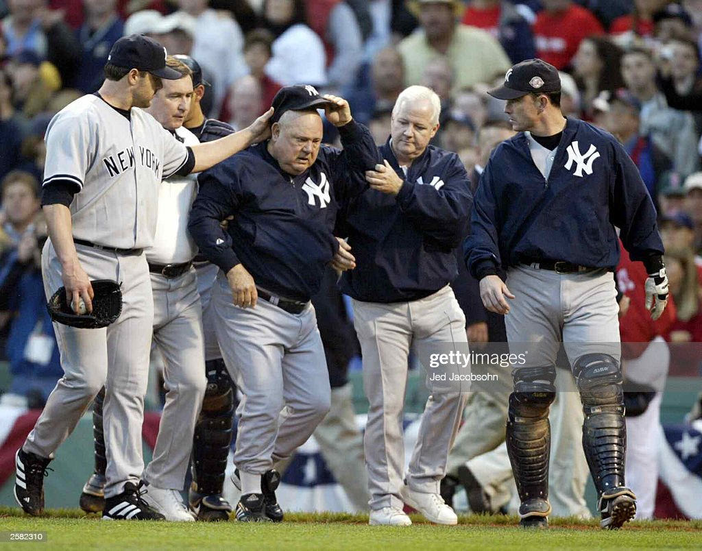 Bench coach <a gi-track='captionPersonalityLinkClicked' href=/galleries/search?phrase=Don+Zimmer&family=editorial&specificpeople=215376 ng-click='$event.stopPropagation()'>Don Zimmer</a> (C) of the New York Yankees is helped back to the dugout by team trainers and pitcher Roger Clemens #22 (L) after Zimmer was thrown to the ground by Pedro Martinez #45 of the Boston Red Sox after he had charged Martinez during the fourth inning of Game 3 of the 2003 American League Championship Series on October 11, 2003 at Fenway Park in Boston, Massachusettes.