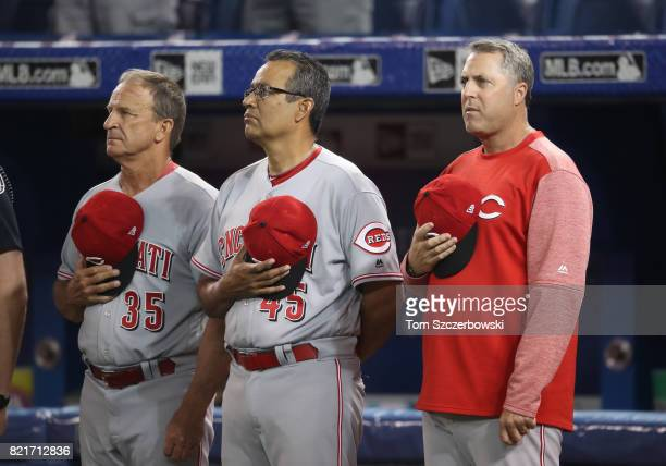 Bench coach Jim Riggleman of the Cincinnati Reds and first base coach Freddie Benavides and manager Bryan Price stand during the playing of the...