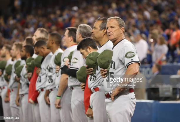 Bench coach Jim Riggleman of the Cincinnati Reds lines up along with the rest of the team for the playing of the anthems before the start of their...
