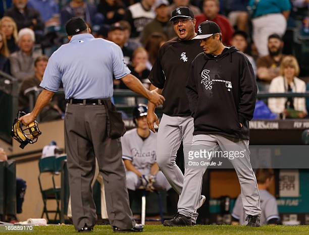 Bench coach Mark Parent of the Chicago White Sox exchanges words with home plate umpire Dale Scott as manager Robin Ventura attempts to keep them...