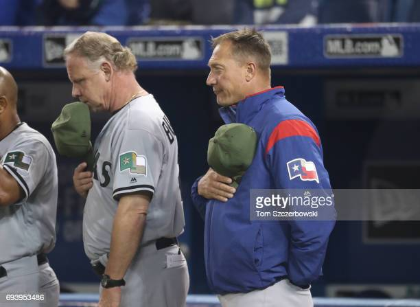Bench coach Steve Buechele of the Texas Rangers and manager Jeff Banister stand for the playing of the American anthem before the start of MLB game...