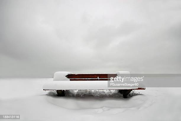 Bench covered with snow at winter