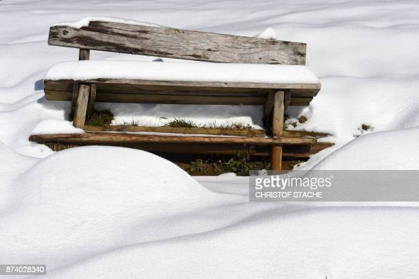 A bench is covered in snow near the Spitzingsee lake in the small Bavarian village of Spitzingsee in the Alp mountains southern Germany during nice...