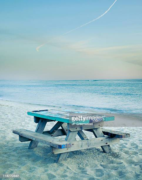 Bench on shoreline of beach