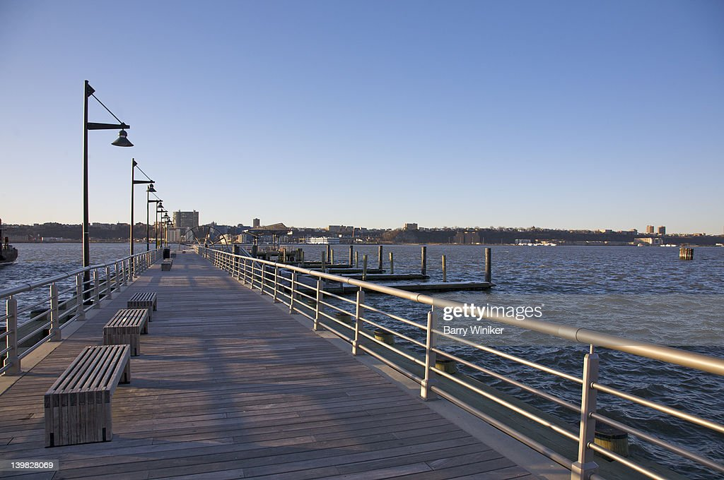 Benches and W. 26th Street Pier extending into the Hudson River, North River, towards New Jersey at foot of Hudson River Park, Chelsea, New York, NY, USA.
