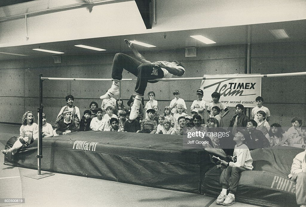 Bending over backwards to pelase fans Canadian decathlete Dave Steen soars over the high jump bar to the delight of a group of school children at U...