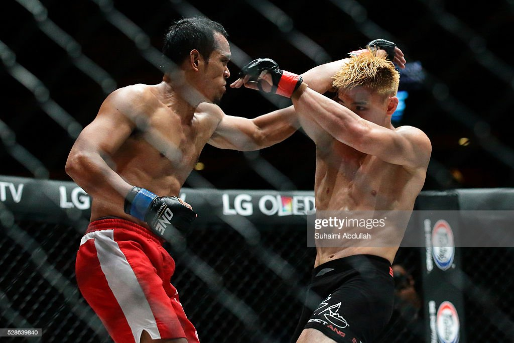 Benedict Ang (R) of Singapore fights Jimmy Yabo of Philippines in the featherweight bout during One Championship: Ascent to Power at Singapore Indoor Stadium on May 6, 2016 in Singapore.