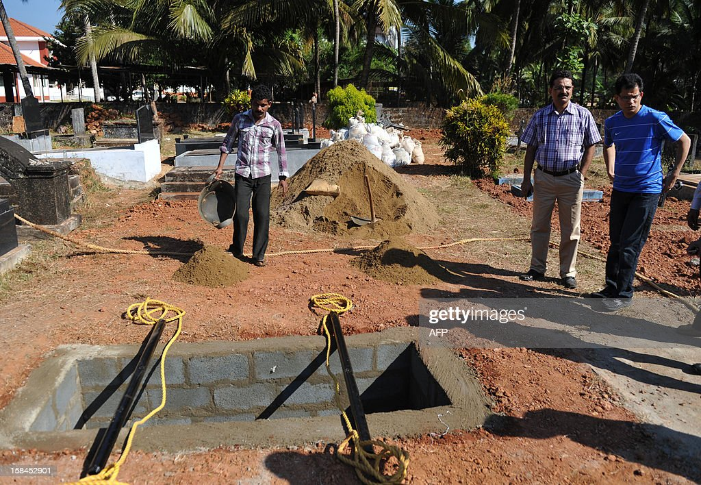 Benedict Barbosa (R), husband of late Indian nurse Jacintha Saldanha inspects preparations of her grave at The Shirva Church Cemetery, near Mangalore on December 16, 2012. Family and friends of the nurse who was found hanged after taking a hoax call to the hospital treating Prince William's wife are preparing for her funeral in a small town in southwest India. Indian-born Jacintha Saldanha, 46, apparently committed suicide after answering the telephone call from two Australian radio DJs to the hospital where the pregnant Duchess of Cambridge was admitted with acute morning sickness. AFP PHOTO/Manjunath Kiran