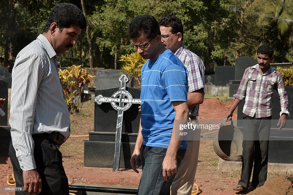 Benedict Barbosa (C), husband of late Indian nurse Jacintha Saldanha, arrives to inspect the preparations of her grave at The Shirva Church Cemetery, near Mangalore on December 17, 2012. Family and friends of the nurse who was found hanged after taking a hoax call to the hospital treating Prince William's wife are preparing for her funeral in a small town in southwest India. Indian-born Jacintha Saldanha, 46, apparently committed suicide after answering the telephone call from two Australian radio DJs to the hospital where the pregnant Duchess of Cambridge was admitted with acute morning sickness. AFP PHOTO/Manjunath Kiran