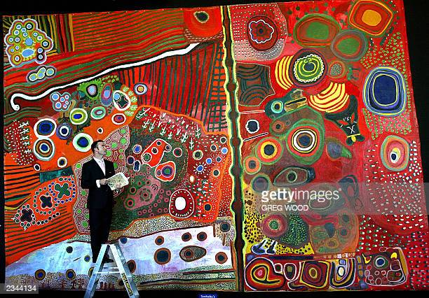 Benedict Pownall from Sotheby's inspects a giant Aboriginal collaborative painting the 'Ngurrara' canvas in Sydney 29 July 2003 A twonight auction of...