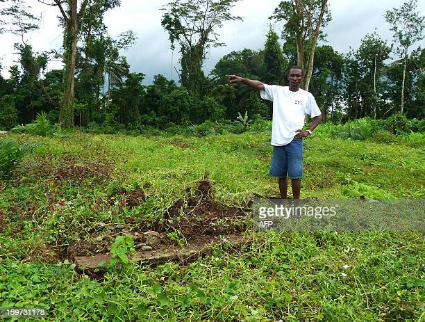 Benedict Smarts stands next to tombs of his ancestors on December 12 on the concession of Indonesian Golden Veroleum Liberia southern Liberia where...