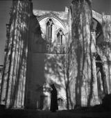 Benedictine monk in meditate in front of the ruins of the transept of the abbeychurch The SaintWandrille abbey about 1935