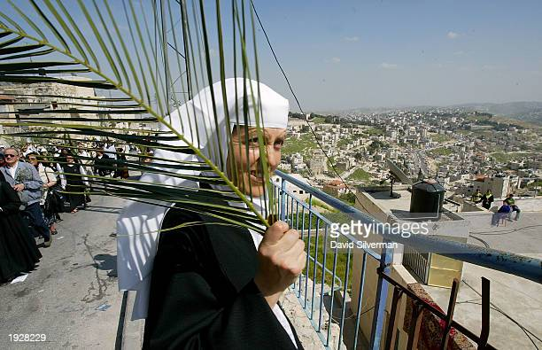 Benedictine nun Sister Marie Veronique of France looks over the Palestinian homes that cover the Mount of Olives as she takes part in the traditional...
