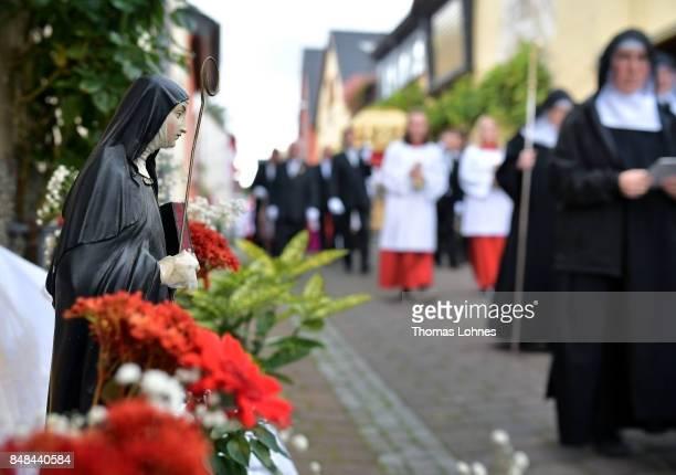Benedictine nuns from Eibingen Abbey pass a small statue of 'Hildegard von Bingen' while the walk in front of the chest that contains the Eibingen...