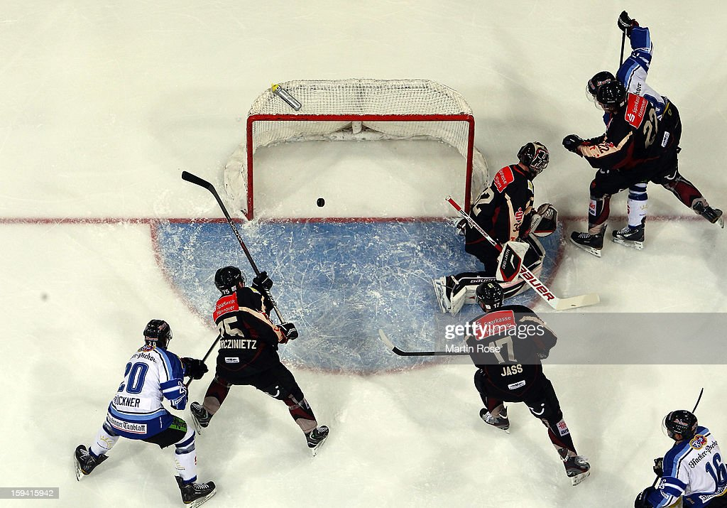 Benedikt Brueckner (#20) of Straubing scores his team's 1st goal over <a gi-track='captionPersonalityLinkClicked' href=/galleries/search?phrase=Dimitri+Paetzold&family=editorial&specificpeople=851119 ng-click='$event.stopPropagation()'>Dimitri Paetzold</a> (C), goaltender of Hannover during the DEL match between Hannover Scorpions and Straubing Tigers at TUI Arena on January 13, 2013 in Hanover, Germany.