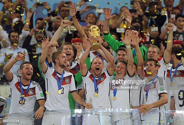 Benedikt Hoewdes of Germany lifts the trophy following the 2014 World Cup Final match between Germany and Argentina at Maracana Stadium on July 13...