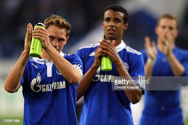 Benedikt Hoewedes Joel Matip and Ralf Faehrmann of Schalke look dejected after losing 02 the Bundesliga match between FC Schalke 04 and FC Bayern...