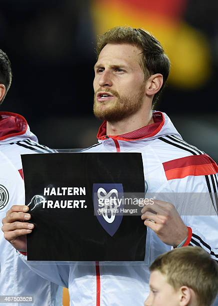 Benedikt Hoewedes of Germany holds up a banner in remembrance of the victims of Germanwings flight 4U9525 prior to kickoff during the International...