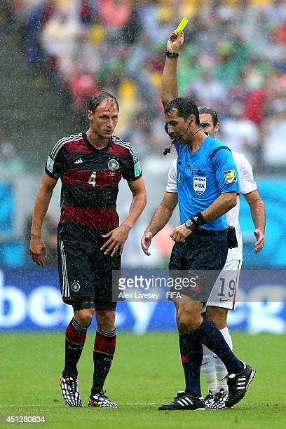 Benedikt Hoewedes of Germany is shown an yellow card by referee Ravshan Irmatov during the 2014 FIFA World Cup Brazil Group G match between USA and...