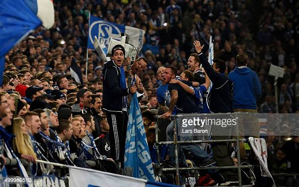 Benedikt Hoewedes of Schalke and goalkeeper Ralf Faehrmann of Schalke celebrate with their team mates and fans after winning the Bundesliga match...
