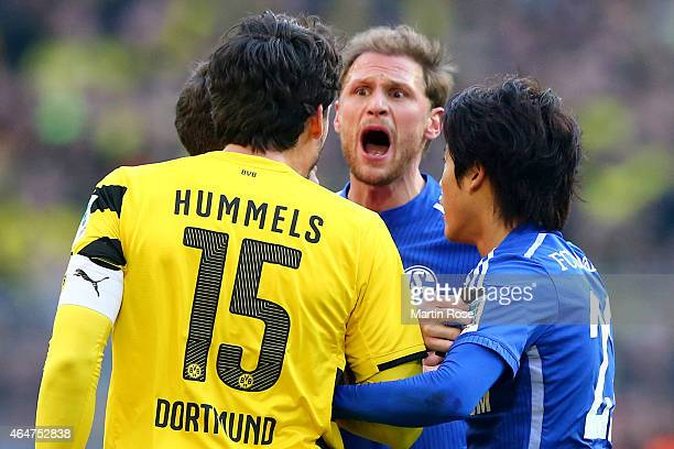 Benedikt Hoewedes of Schalke and his team mate Atsuto Uchida react to Mats Julian Hummels of Dortmund during the Bundesliga match between Borussia...