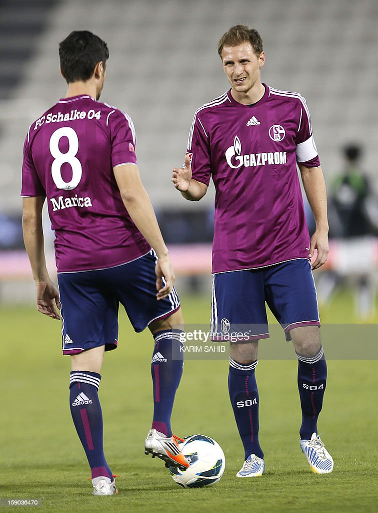 Benedikt Hoewedes of Schalke (R) and Romanian forward Ciprian Marica (L) celebrates their team's third goal during their friendly football match in Doha on January 6, 2013. Schalke is in Qatar for a week-long training camp before the beginning of the new season of the German Bundesliga after the winter break.