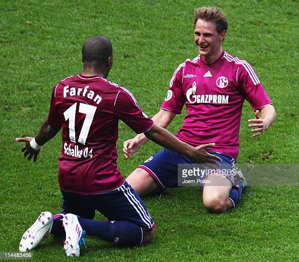 Benedikt Hoewedes of Schalke celebrates with his team mate Jefferson Farfan after scoring his team's third goal during the DFB Cup final match...