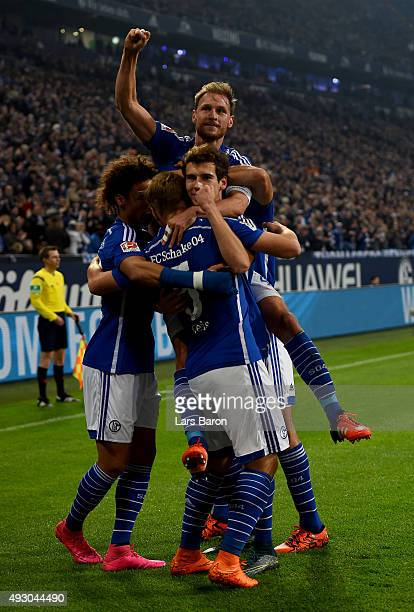 Benedikt Hoewedes of Schalke celebrates with team mates after scoring his teams first goal during the Bundesliga match between FC Schalke 04 and...