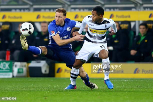 Benedikt Hoewedes of Schalke challenges Raffael of Moenchengladbach during the Bundesliga match between Borussia Moenchengladbach and FC Schalke 04...
