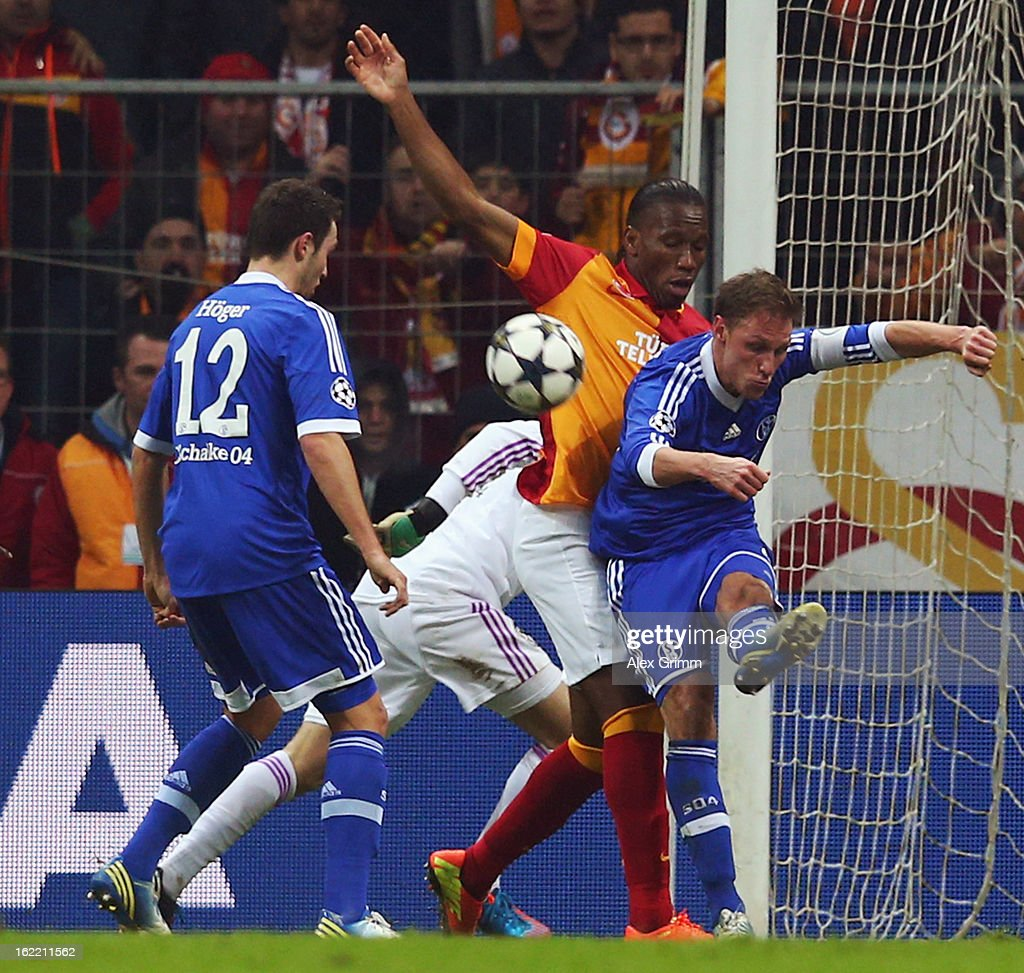 Benedikt Hoewedes of Schalke clears the ball ahead of Didier Drogba of Galatasaray during the UEFA Champions League Round of 16 first leg match between Galatasaray and FC Schalke 04 at the Turk Telekom Arena on February 20, 2013 in Istanbul, Turkey.