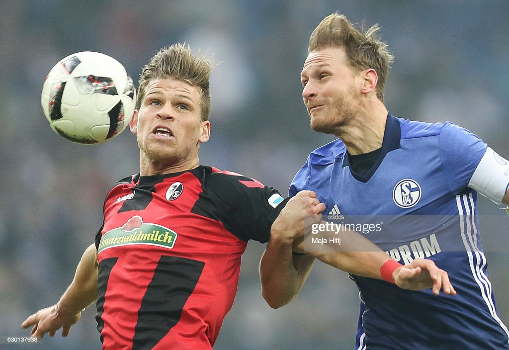 Benedikt Hoewedes of Schalke is challenged by Florian Niederlechner (L) of Freiburg during the Bundesliga match between FC Schalke 04 and SC Freiburg at Veltins-Arena on December 17, 2016 in Gelsenkirchen, Germany.