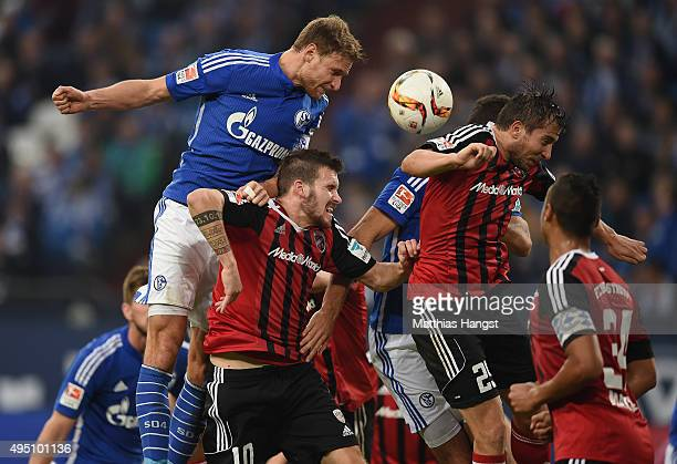 Benedikt Hoewedes of Schalke jumps for a header with Pascal Gross of Ingolstadt and Markus Suttner of Ingolstadt during the Bundesliga match between...