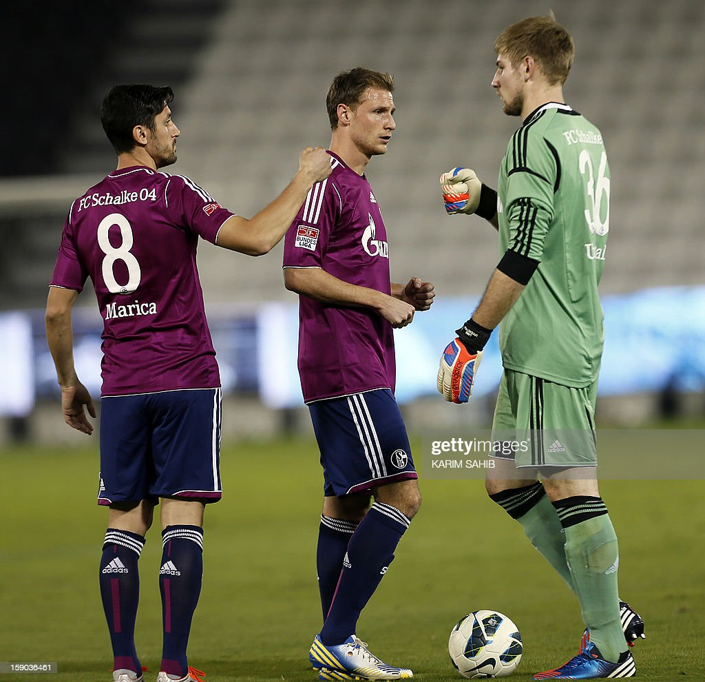 Benedikt Hoewedes of Schalke (C) Schalke's Romanian forward Ciprian Marica (L) and Lars Uannerstall (R) celebrates their team's third goal during their friendly football match in Doha on January 6, 2013. Schalke is in Qatar for a week-long training camp before the beginning of the new season of the German Bundesliga after the winter break.