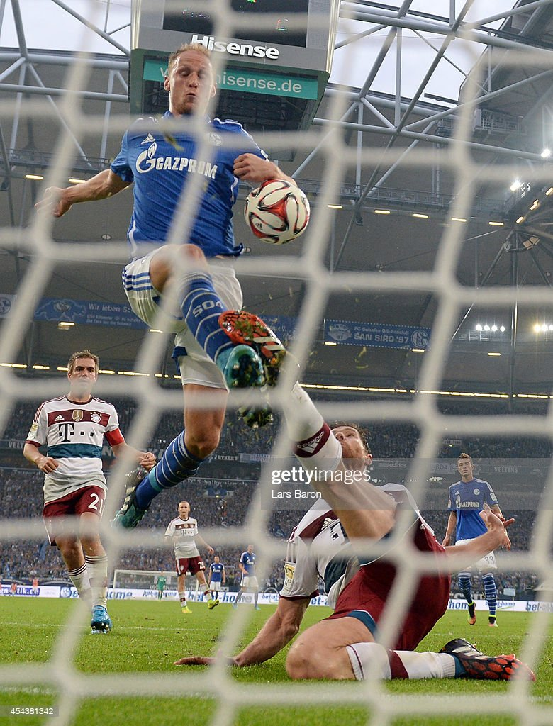 Benedikt Hoewedes of Schalke scores his teams first goal past Xabi Alonso of Muenchen during the Bundesliga match between FC Schalke 04 and FC Bayern...