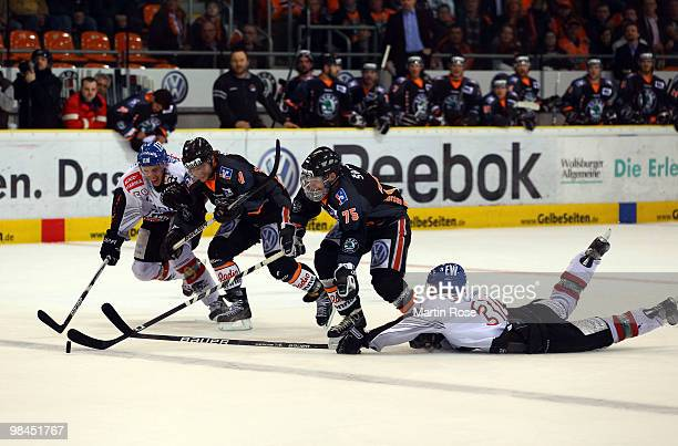 Benedikt Kohl of Augsburg tries to stop Andreas Morczinietz of Wolfsburg during the third DEL play off semi final match between Grizzly Adams...