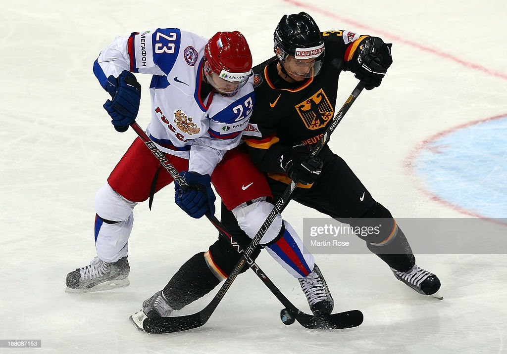 Benedikt Kohl (R) of Germany and Denis Kokarev (L) of Russia battle for the puck during the IIHF World Championship group H match between Germany and Russia at Hartwall Areena on May 5, 2013 in Helsinki, Finland.