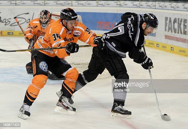 Benedikt Kohl of Wolfsburg challenges Patrick Reimer of Nuremberg during game three of the DEL preplayoffs between Thomas Sabo Ice Tigers and Grizzly...