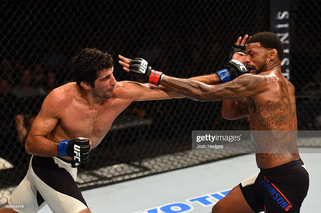 Beneil Dariush punches Michael Johnson in their lightweight bout during the UFC Fight Night event at Bridgestone Arena on August 8, 2015 in Nashville, Tennessee.