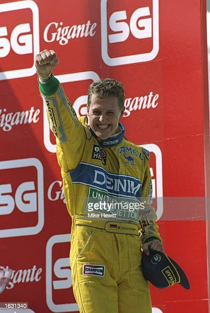 Benetton Ford driver Michael Schumacher of Germany waves a fist to the crowd as he stands on the winners'' podium after his victory in the Portuguese...