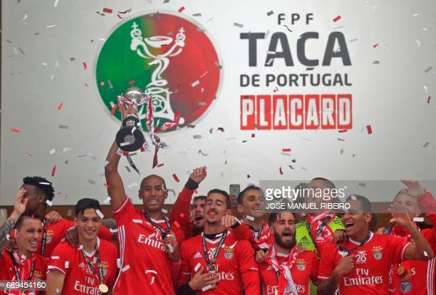 Benfica captain Brazilian defender Luisao holds up the cup to celebrate with teammates after winning the Portugal's Cup at the end of the final...