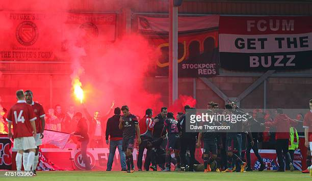 Benfica fans run onto the pitch to celebrate with players after the only goal of the game during the friendly match between FC United Of Manchester...