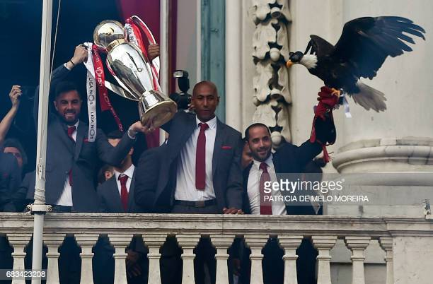 Benfica football players raise their trophy and their bald eagle mascot at Lisbon's City Hall as they celebrate their victory in the 20162017...