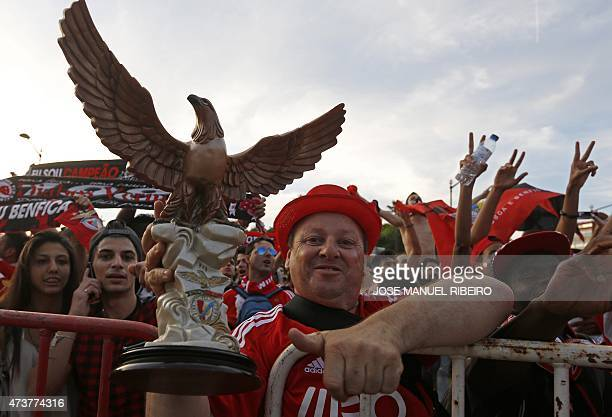 A Benfica supporter holds an eagle trophy as others celebrate their team's 34th Portuguese league title in central Lisbon on May 17 2015 after the...
