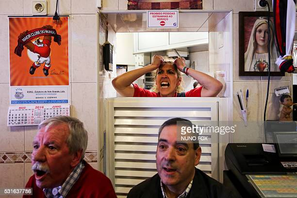 TOPSHOT Benfica supporters watch the Portuguese League football match SL Benfica vs CD Nacional on television at 'A Ginginha' restaurant in downtown...
