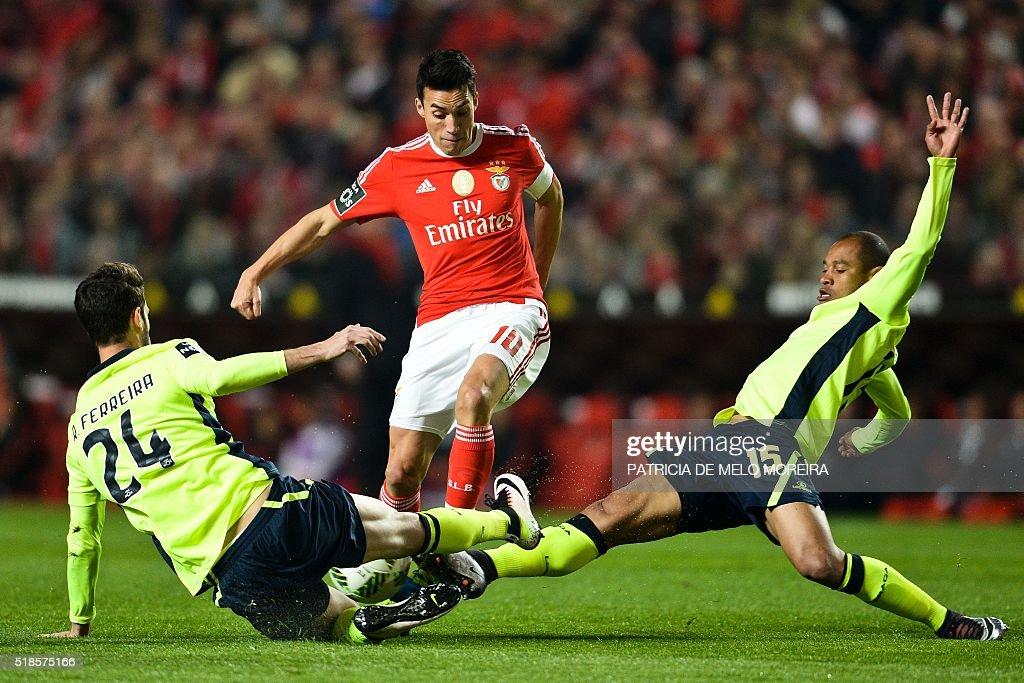 Benfica's Argentine midfielder Nicolas Gaitan vies with Braga's defender Ricardo Ferreira and Braga's Brazilian defender Baiano during the Portuguese...