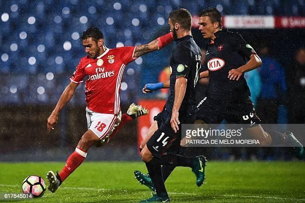Benfica's Argentinian midfielder Eduardo Salvio vies with Belenenses' defender Domingos Duarte and Belenenses' midfielder Joao Palhinha during the...