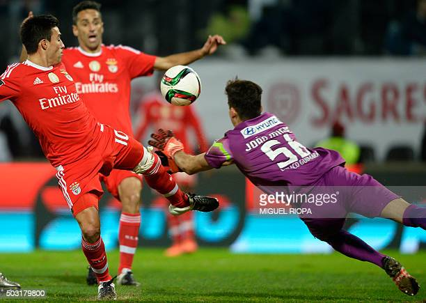 Benfica's Argentinian midfielder Nicolas Gaitan misses an attempt on goal next to Vitoria Guimaraes' goalkeeper Miguel Silva during the Portuguese...
