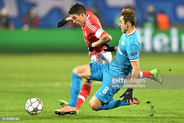 Benfica's Argentinian midfielder Nicolas Gaitan vies for the ball with Zenit's Brazilian midfielder Mauricio during the secondleg round of 16 UEFA...